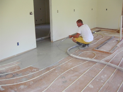 Pouring lightweight concrete over radiant floor heat system